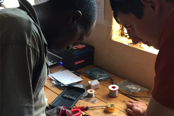 Image of two men working on a battery pack